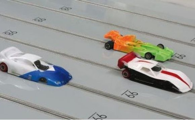 three-toy-racing-scaletrix-cars-on-grey-track-middle-one-winning